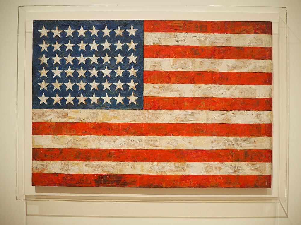 """A photo of Jasper Johns' painting called """"Flag"""" at the Museum of Modern Art in NYC. It has 48 starts and more texture than an actual flag, but otherwise just looks like the flag."""