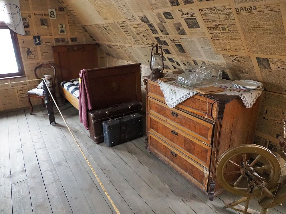 The wall is slanted under the roof and wallpapered with newspaper. A bureau with a few objects on it: glasses, a lantern, some plates. A spinning wheel is partially in view in front of that. Beyond the bureau is a single bed and at its foot, two suitcases. Next to the bed is a chair with a doll sitting on it.