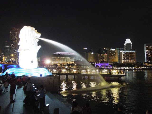 The Merlion statue is on the left of the picture, brightly lit up, as is the water spewing from its mouth to the right, into the river. It's nighttime, and tall buildings are in the background, with white lights in some of the windows against a black sky.