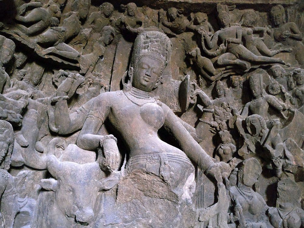 The central figure is a woman, standing with her hip jutting out to the right. From the hips down is destroyed. Around her are many smaller figures in different poses, some quite damaged but some intact and detailed.