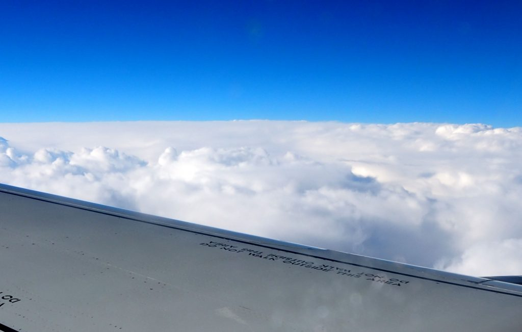 A view over an airplane wing onto fluffy white clouds. Above them, brilliant blue sky.