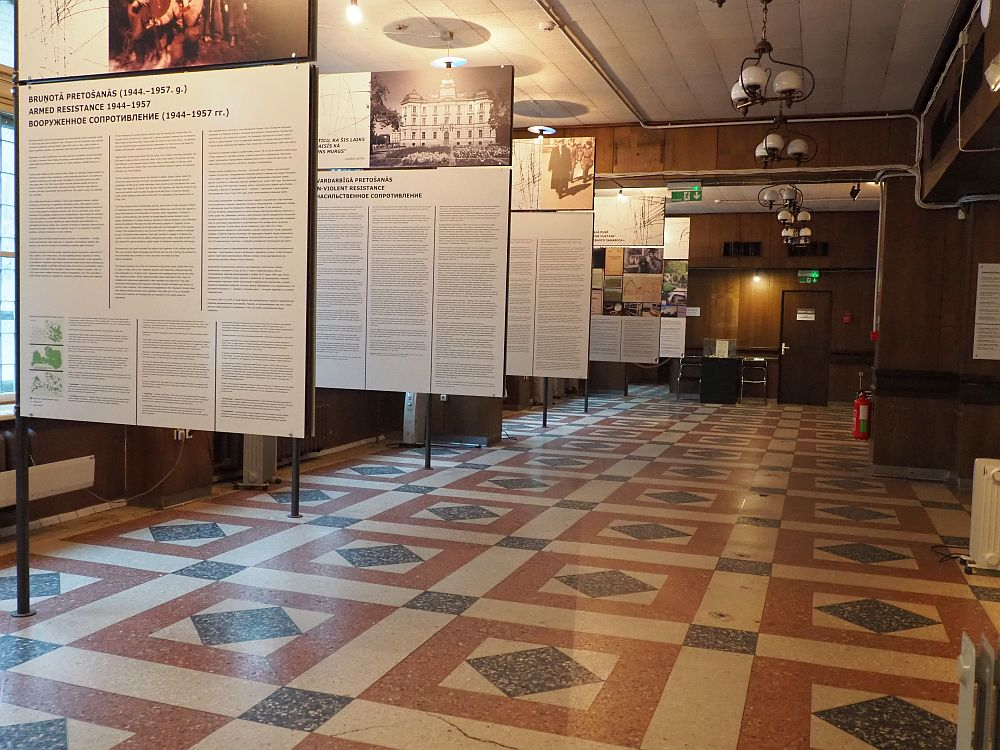 A large room, the floor in neat tile squares. Along the left, where the windows are, stand a series of 5 large sign, perpendicular to the left wall. Each is printed with some of the history with a photo at the top. The history is written three times: in Latvian, in English and in Russian.