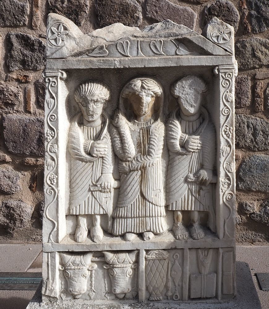 The grave marker is carved so that three human figures stand in a framed niche. The one in the center may be a woman: the robe is longer and he/she wears a hood as well. The ones on either side each hold something in their left hands - a scroll, perhaps? - nd have their right hands in a sort of sling. The faces are eroded or damaged. Around the frame grape leaves are carved. Below the feet of the three figures are smaller frames. The one on the left has the faces of two cows or oxen. The one in the middle shows a basket or perhaps a fish trap. And the one on the right isn't clear.