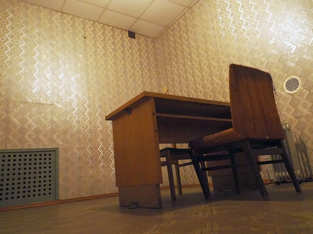Photo taken from ground level, looking upwards. Two walls of the room are visible, covered with ugly wallpaper in a zigzag design in shades of gray. A wooden table stands in the middle with a straight chair on either side.
