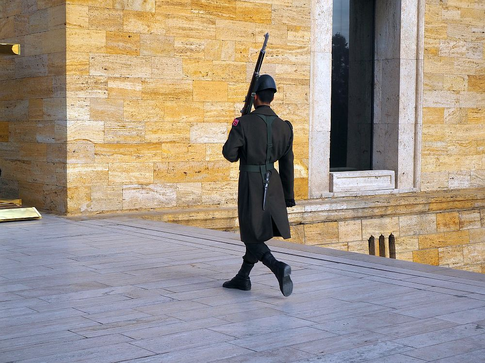 The guard is walking away and to the left. He wears a black trenchcoat, black pants, black socks and black shoes and a black hat too. He has a knife hanging from his belt and carries a long with his left hand, leaning the gun on his shoulder, pointing upwards.