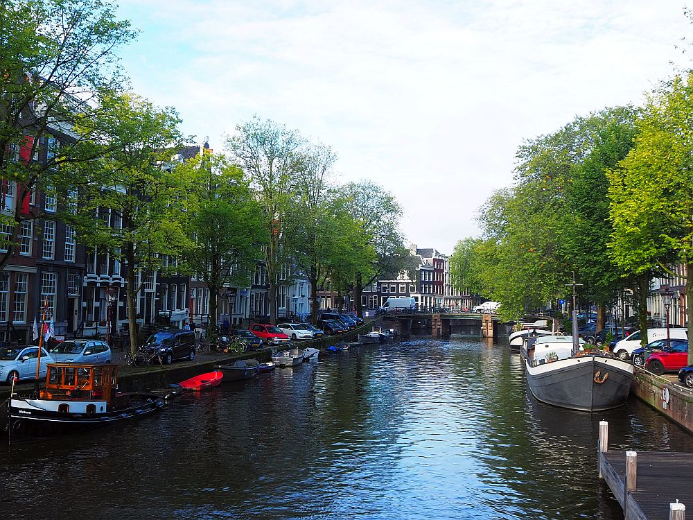A view down a canal. Row houses on either side, boats moored along the side, a bridge crossing it in the distance.
