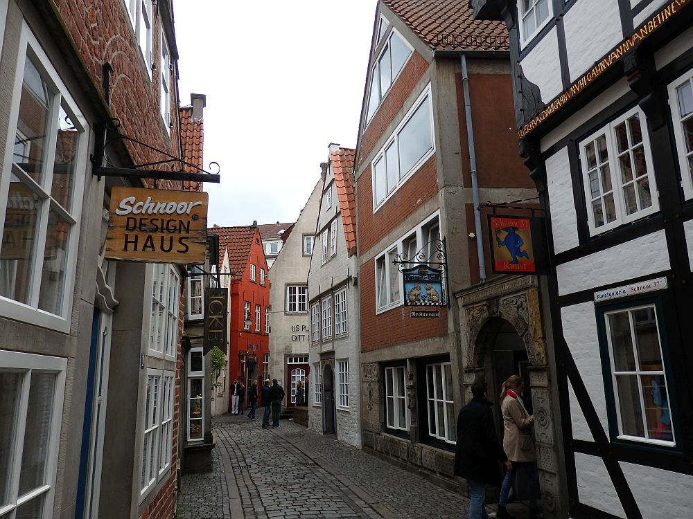 A narrow cobbled street. the houses vary in age. Some have exposed timbers and many lean a bit one way or another.