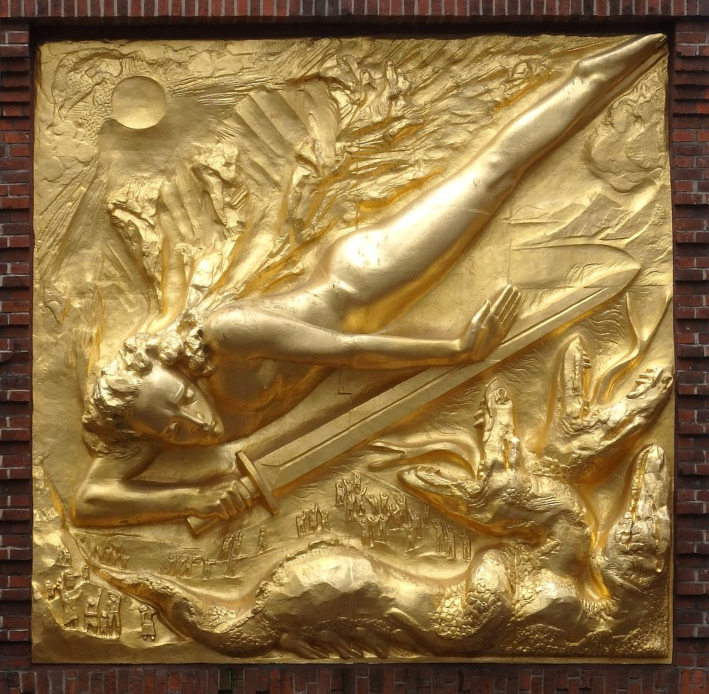 The bas-relief portrays a figure of a human angled from top right to bottom left, head downward. He/she holds a very long sword, pointing to top right. Some sort of creatures, perhaps dragons, are lower right. The whole thing is shiny gold.
