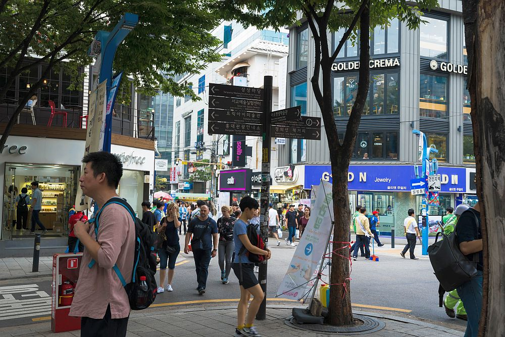 A view of an intersection of Hongik University Street. People are walking both in the street and on the sidewalks in all directions. Many look like students, carrying backpacks. Trees on the corner in the foreground, buildings in the background with shops on the ground floor.