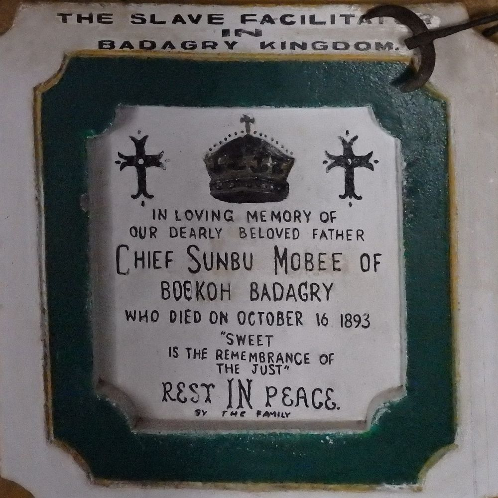 """A plaster sign, white with a green frame around it. Above the sign it reads """"The slave facilitator in Badagry Kingdom."""" and inside the frame it reads, under a picture of a crown and two crosses: """"In loving memory of our dearly beloved father Chief Sunbu Mobee of Boekoh Badagry who died on October 16 1893 """"Sweet is the remembrance of the just"""" Rest IN Peace. By the family"""""""