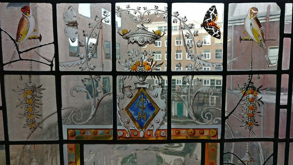 The glass is divided in rectagular panes. The center one has a small coat of arms with a brown frame and blue background. It looks like a decorative form of C, I and H on the blue background. Sitting on top of the coat of arms is a vase with orange flowers, and above that, an odd little silver roof, with a snail on either side. Other animals are on nearby panes: a bird on either side, a butterfly on each side too. Also a bunch of what looks like grapes, but with orange flowers hangs on either side of the coat of arms. Between the paintings, the glass is clear, allowing a view of the garden.