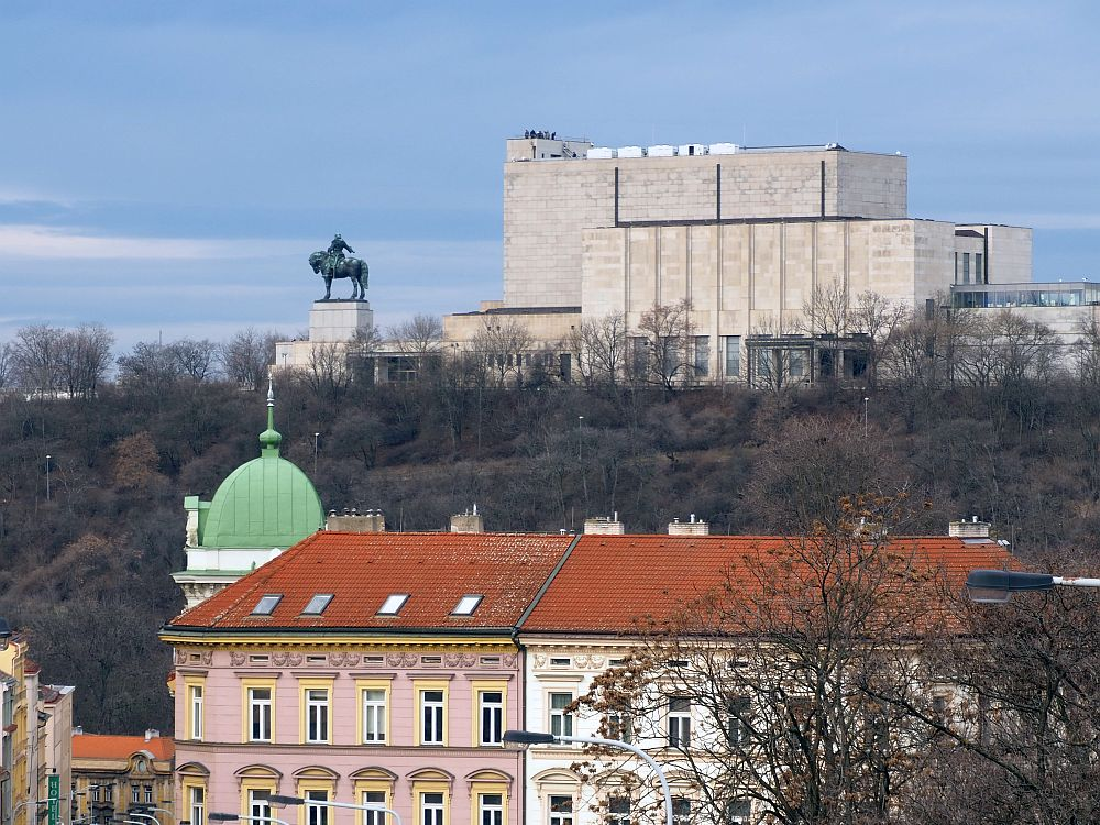A very large block of a building on a rise, with an equestrian statue to its left. The statue must be quite large to be so visible from such a distance. Below the ridge are some more typical older buildings: one in pink with yellow edging and one in white, both with decorative elements around the window. A green dome peeks from behind one of the buildings. The side of the hill between the older buildings and the mausoleum is tree-covered.