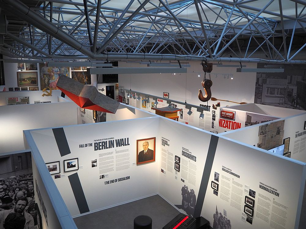 """The space has a high roof with a latticework of bars holding up a translucent glass ceiling. Below, the walls around the exhibit spaces are normal wall height but without ceilings, so from this viewpoint the contents of the rooms are visible. The nearest room has titles painted on the wall that read """"Fall of the Berlin Wall"""", """"Dissidents"""" and """"Normalization."""" The rest is not legible form this distance."""