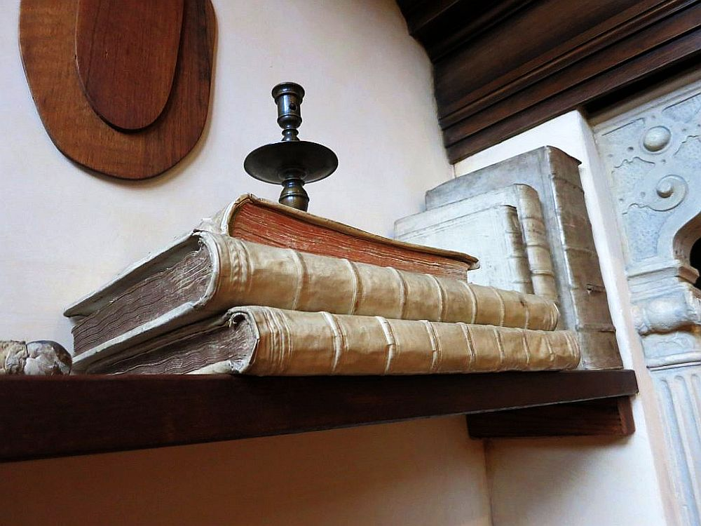 A detail from the shelf in Rembrandt's studio in Rembrandt House Museum: two large white bound books lie on their side, another smaller book on top of them and a candlestick on that. Beyond are three more bound books, standing agains the wall at the end of the shelf.