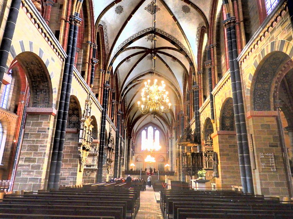 A typical medieval cathedral structure, with columns along the sides and gothic arches in the ceiling. Photo looks the length of the nave from the center aisle between the pews, to the altar in the far distance, blurry because of the light coming in the windows behind the altar.
