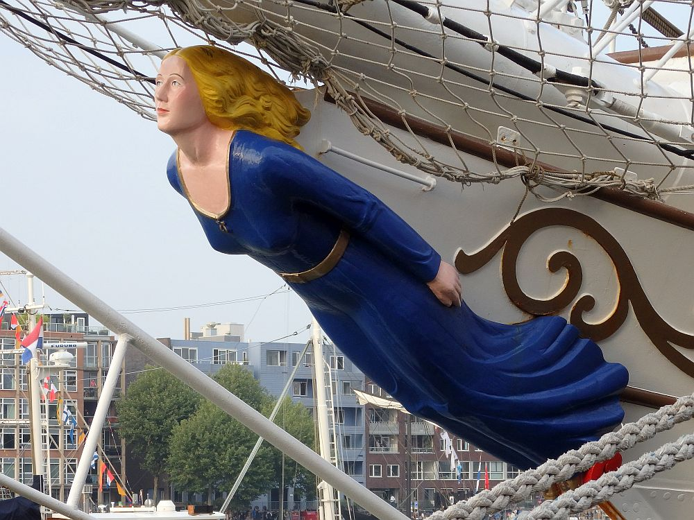 A figurehead of carved wood in the shape of a woman. She is carved under the bow of a ship, so her back is attached while her front is visible. She wears a simple long, blue dress with a scoop neck. She is white with blond hair streaming behind her.