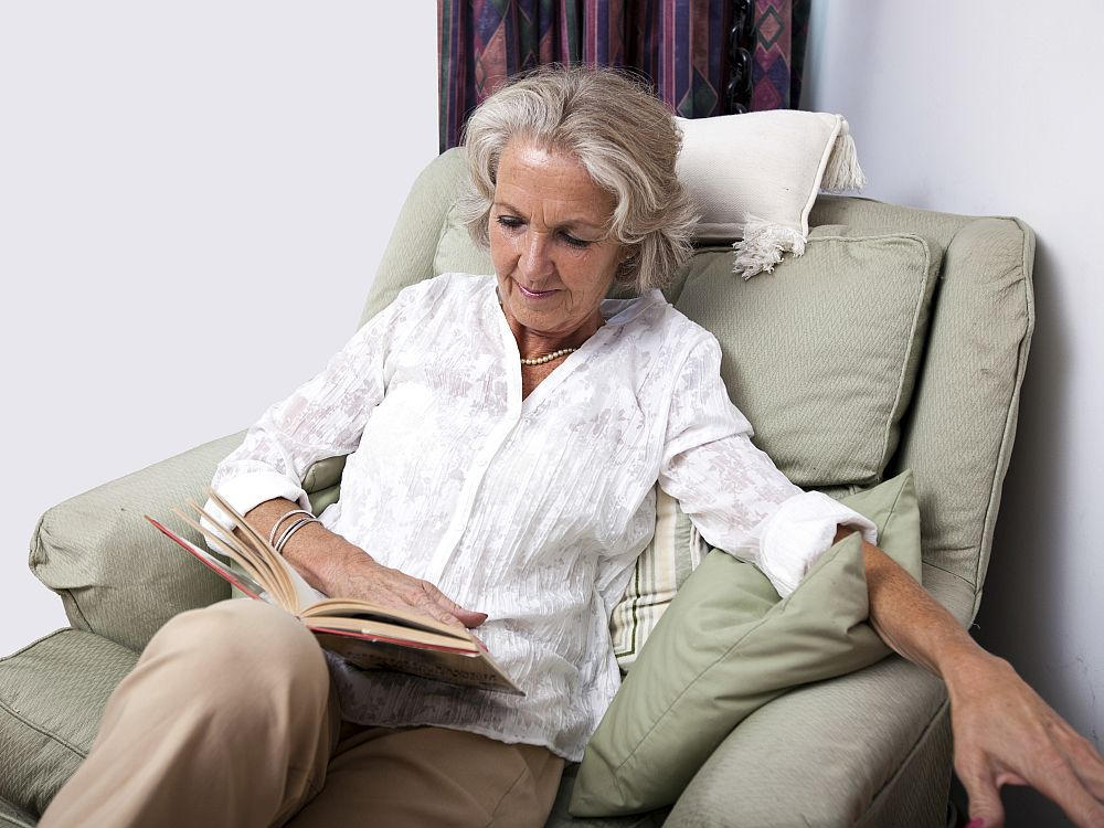 A grey-haired white woman sits in a comfy-looking armchair reading a book. She wears a plain white blouse and beige trousers and has a string of pearls around her neck.