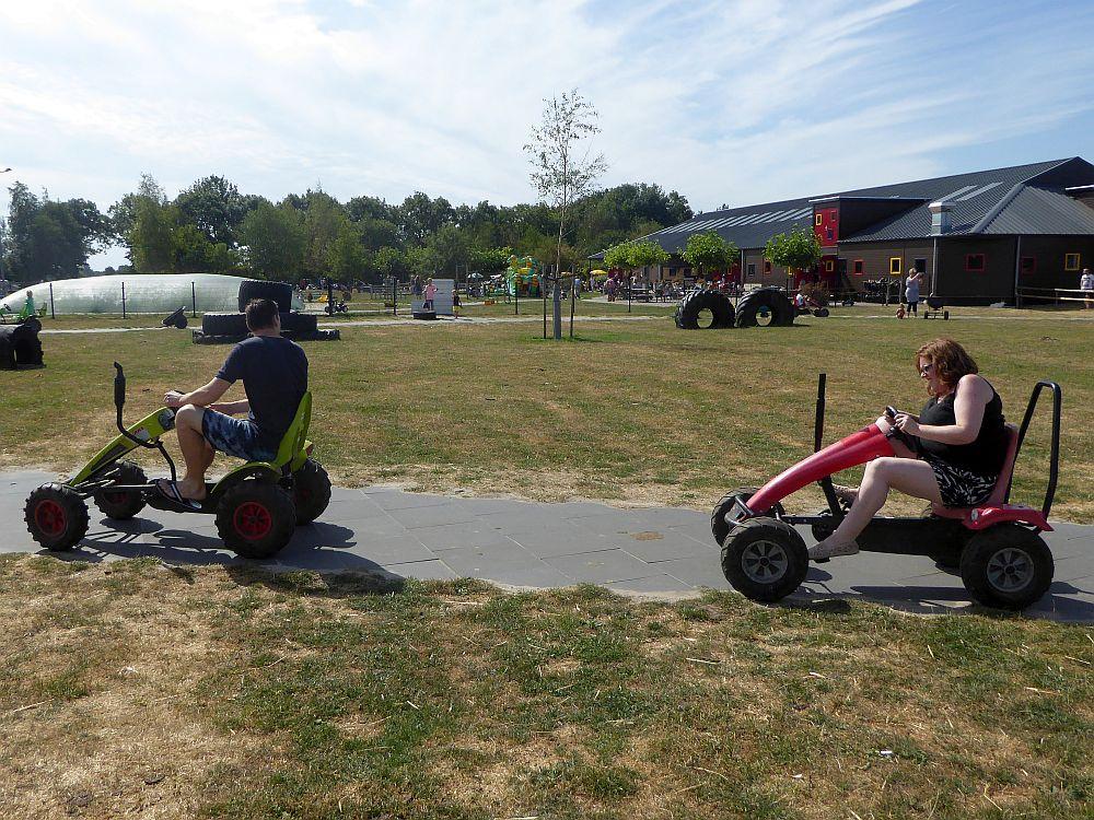In the foreground, two people (adults) ride some sort of four-wheeled pedaled vehicles. In the background a bouncy structure and various other play structures can be seen, as well as a very large barn.