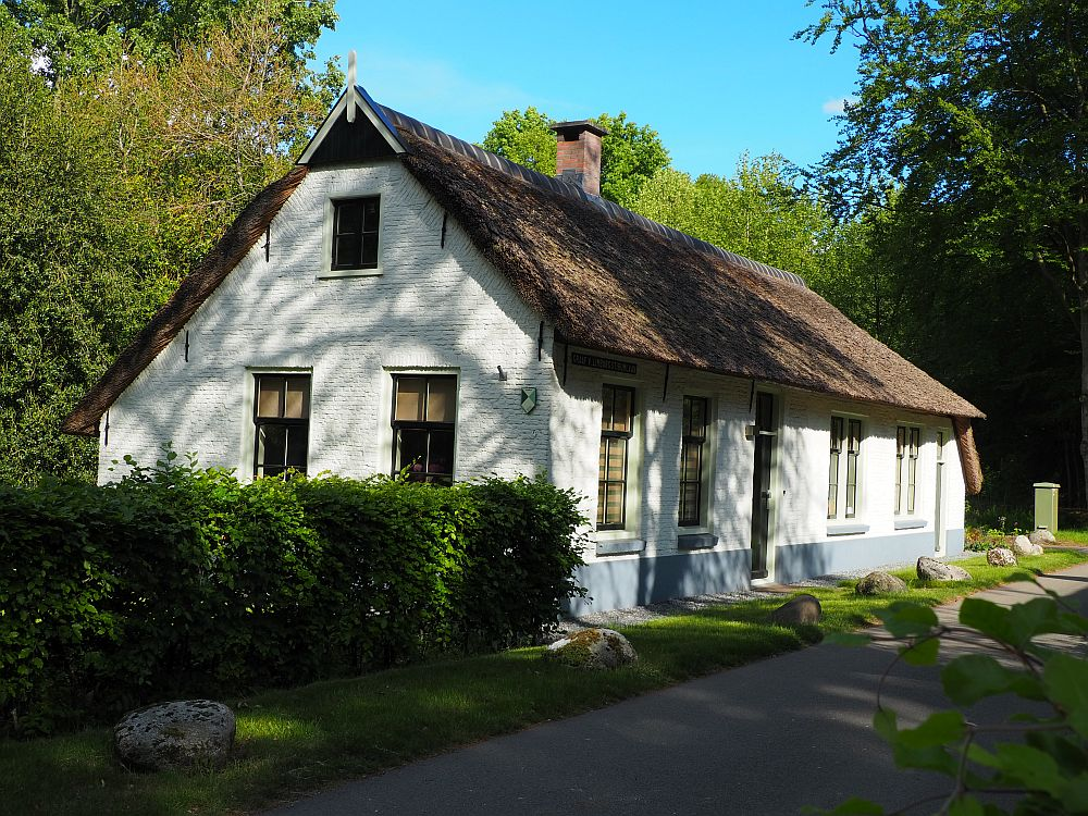 The house is brick, but painted white with a thatched roof. It seems to be one story, but the peak on the end has one upper window as well, implying an attic of some sort. The house is a long rectangle with two doors and four windows on the long side (It might have been a duplex) and two windows (and the attic window above) on the short side.