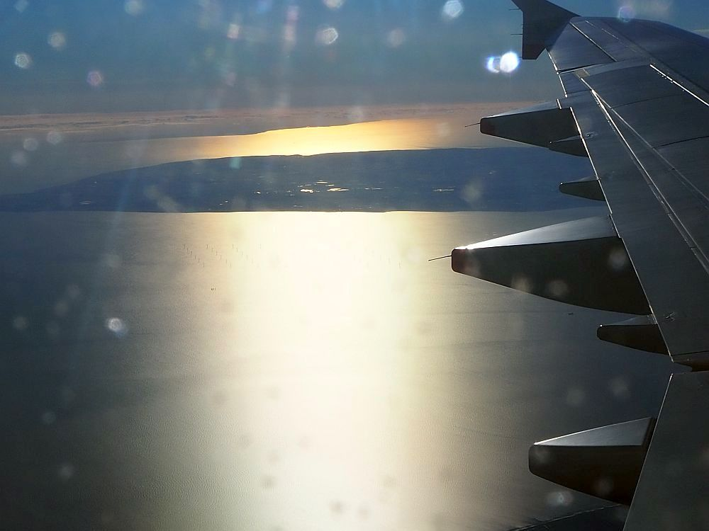 Looking out at the wing from a seat just behind the wind. Along the right side of the photo, only the back edge of the wing is visible. Below is the sea and a flat bit of land in the background. The sun makes the water shine yellow down the center. The sight is scary for a fearful flyer.