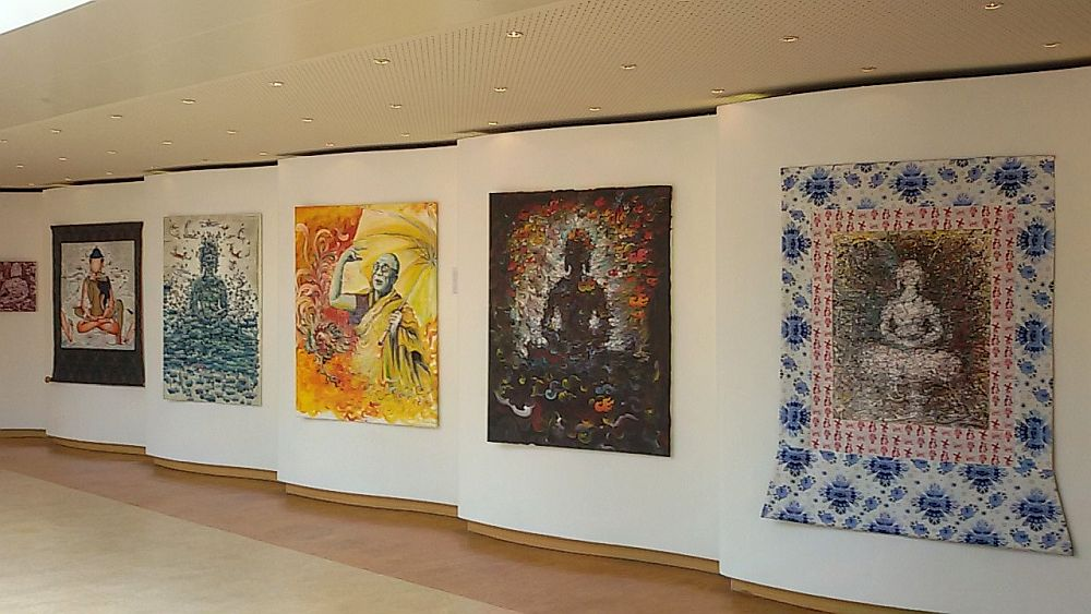A row of 5paintings, all quite large. Each seems to be a very different style, and they seem to be Buddha images or similar, except the center one, which clearly depicts the Dalai Lama. The styles of them all are fairly modern.