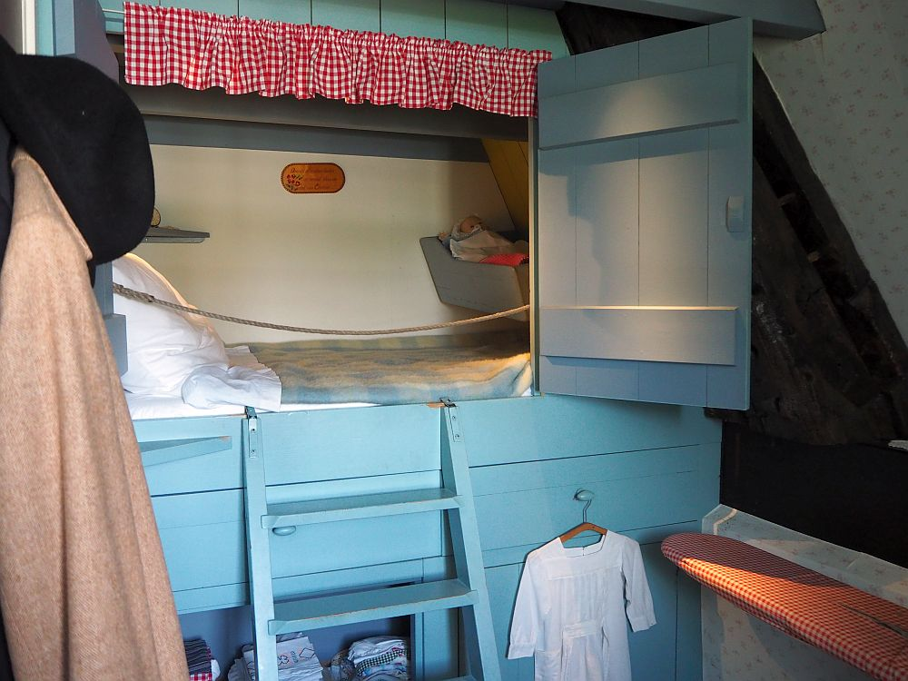 The bed is built into a wall, with a blue painted door standing open. A small ladder of just a few steps, also blue-painted, leads to the bed, which appears quite small. Under the bed are some shelves. Inside, the mattress, blanket and pillows are visible. At the foot of the bed, inside the bedstee as well, a small cradle seems to be mounted on the wall.