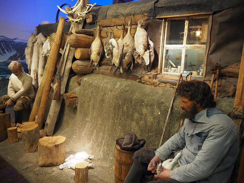 A log cabin with one small window. Hanging next to the window are a number of dead birds: geese or ducks. On the right side of the picture a man sits, and it looks like he's doing something to a dead animal, maybe a fox: perhaps skinning it. There's another lying on the ground. On the left side of the picture another man sits in front of a bunch of arctic fox furs hanging on the wall of the cabin.