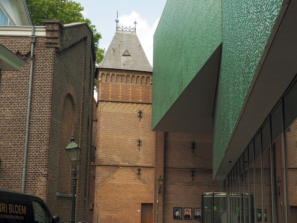 Looking down a narrow road. On the right is the museum: a green, windowless, massive wall above the ground floor, which is glass-sided. On the right, a brick building (the back of the synagogue). Ahead, a brick tower.