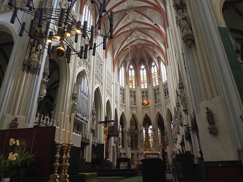A very high-ceilings space with gothic arches all around it and stained glass between the arches. The ceiling is painted and every pillar betwen the arches has a sculpture of a saint on it.