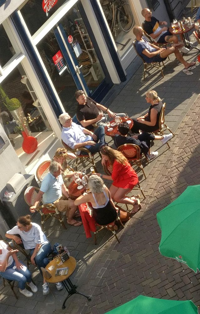Groups of people sit outside on the sidwalk on chairs around small tables  where drinks stand. I don't know if these are family groups, but even if they are, the tables are too close together for safe distancing.