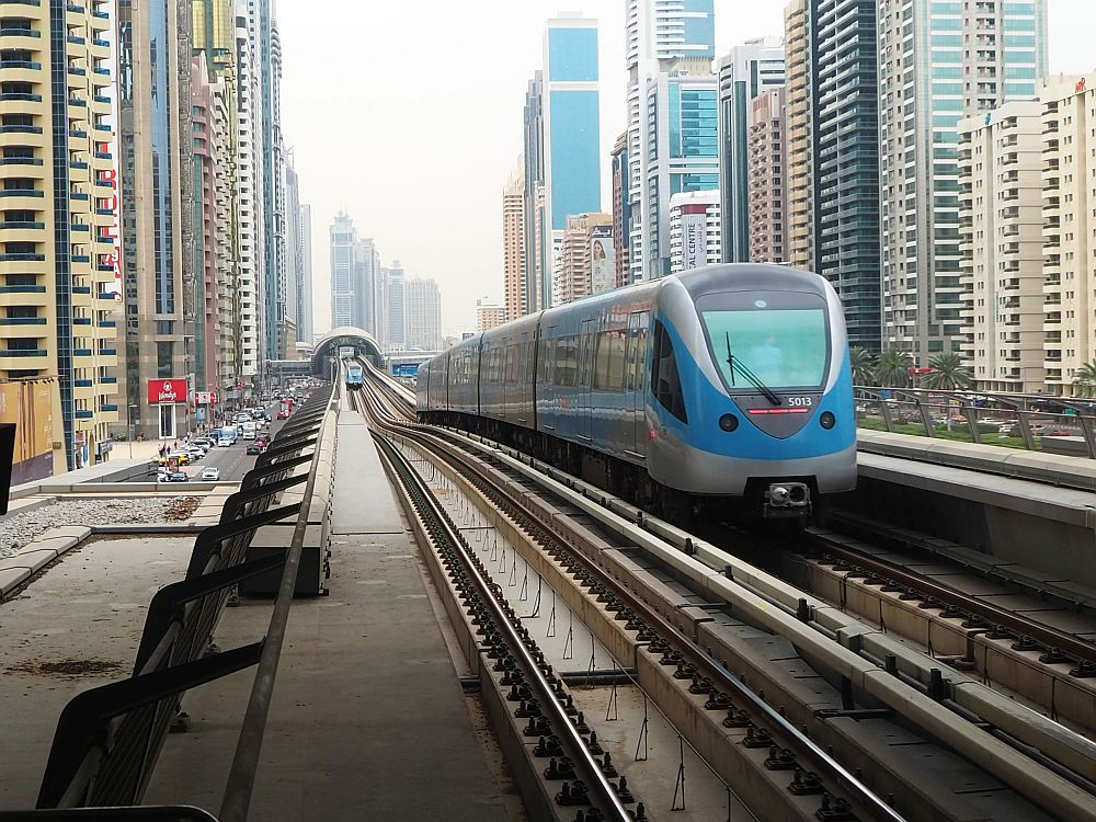 A view down the metro tracks. The tracks run down a street, but above street level, lined with skyscrapers on both sides. A train of several cars in nearby on one set of tracks and another is farther away, approaching on the nearer tracks.