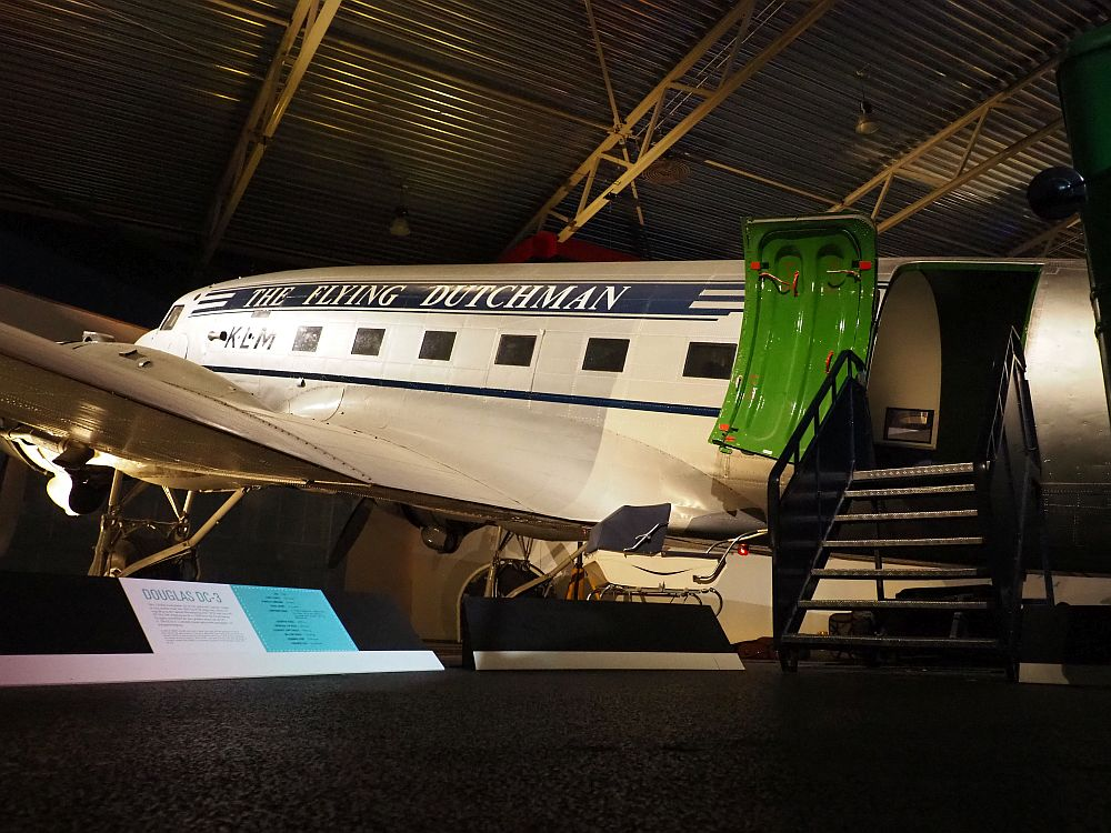 """A more modern-looking airplane slants up to the left. It is painted white with a blue stripe along the length of it, in which the words """"THE FLYING DUTCHMEN"""" are painted in white. The windows are rectangular. The door is open and a short flight of stairs leads up to it."""