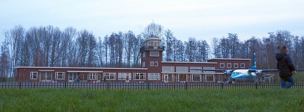 A long, low, brick building, mostly just one story, though on the right-hand end it's two stories. The control tower is in about the center and is about four stories high. It's al very simple, with white-edge windows, and a small balcony around the top floor of the control tower. In front of the building, to the right, is an airplane.
