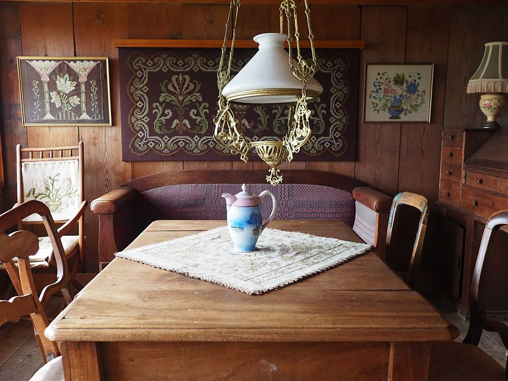 The rooms is mostly filled with a rectangular wooden table and the four chairs around it. A white glass lamp hangs above it. Beyond is a sofa against the far wall. Above the sofa is what looks to be a decorative rug with embroidery on either side of it.