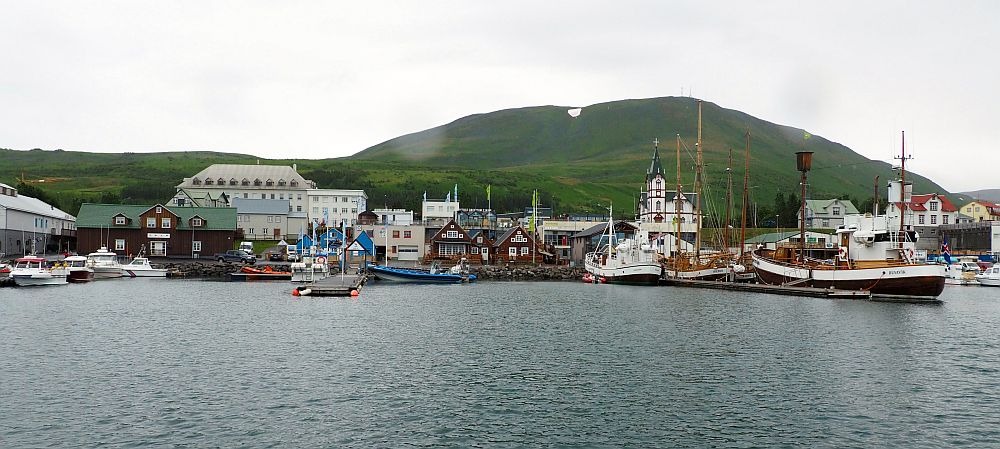 Husavik whale watching leaves from this harbor. Cluster of buildings along the water's edge, several large oak boats moored along a pier on the right. A mountain behind the village with a bit of snow on top. Grey water in the foreground, white sky.