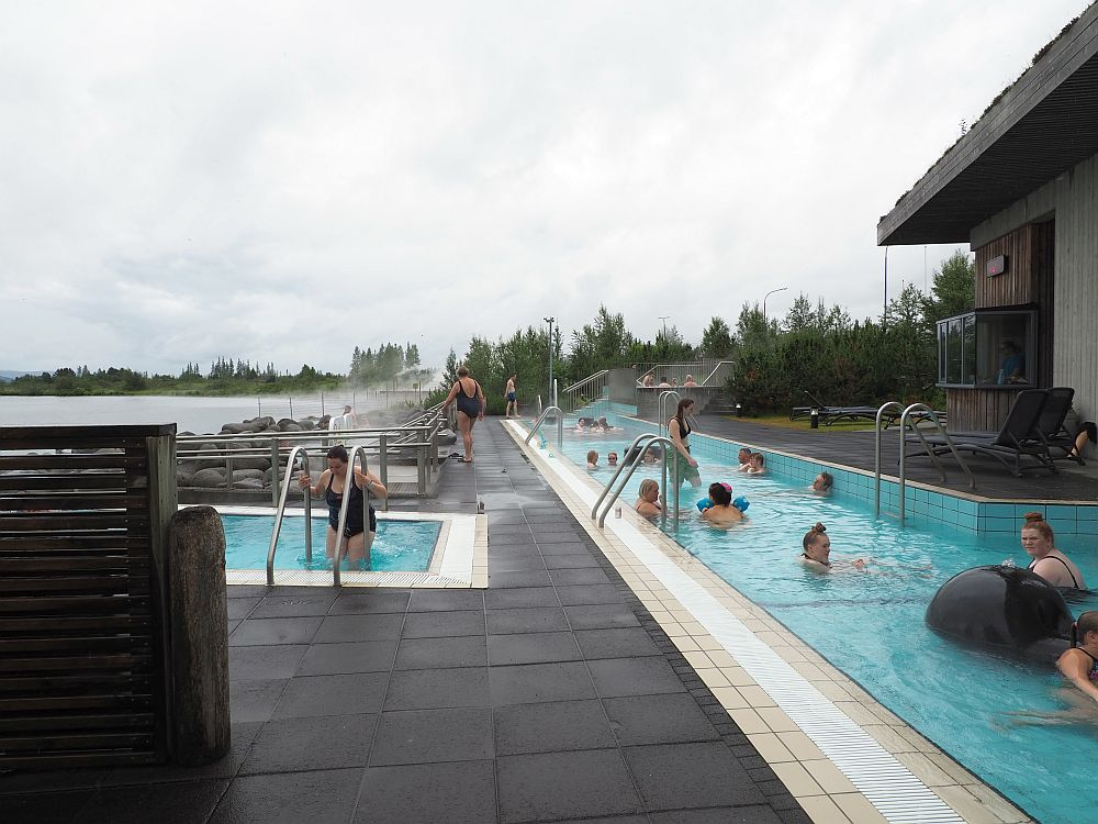 On the right and stretching out straight head is a long shallow pool of clear blue water with a scattering of people sitting in it. On the left, part of another pool is visible. The water is the same color and a woman is climbing the ladder to get in. Steam rises beyond the small pool on the left.