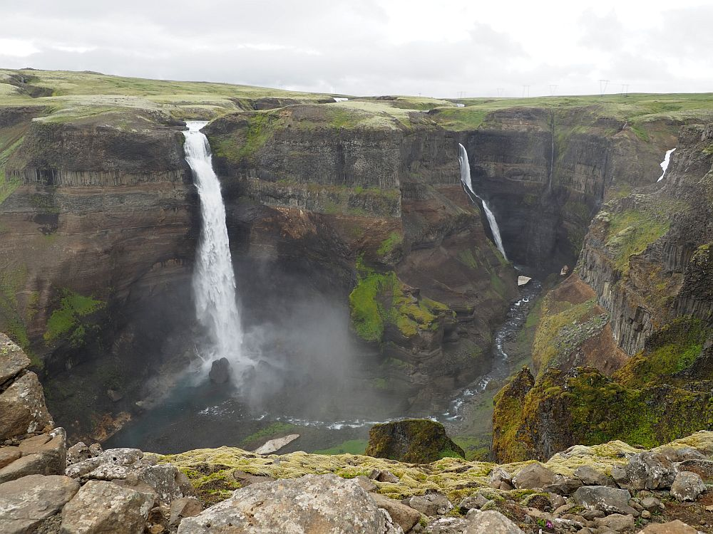 Two waterfalls in this photo: both are long and narrow and fall of the same cliff to a stream in a canyon. Both are white, and the nearer one is wider.