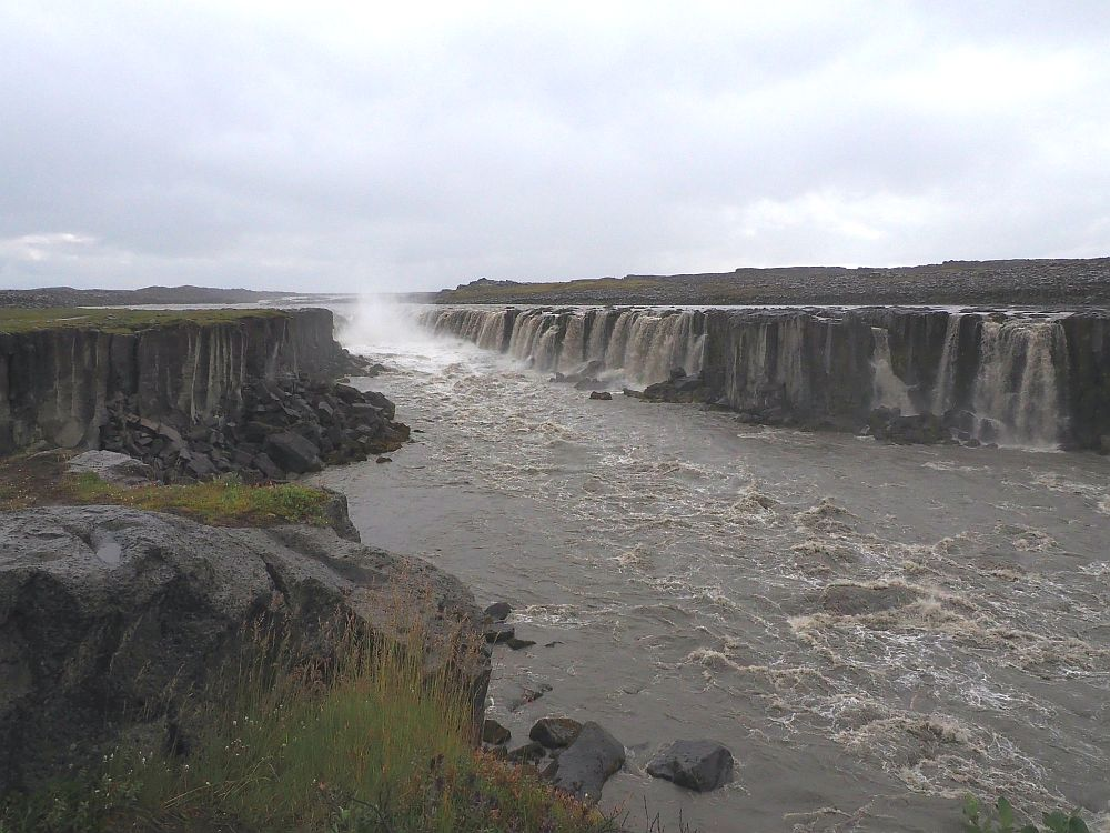 Looking up the river, a series of waterfalls line the opposite bank, made up of a long cliff.