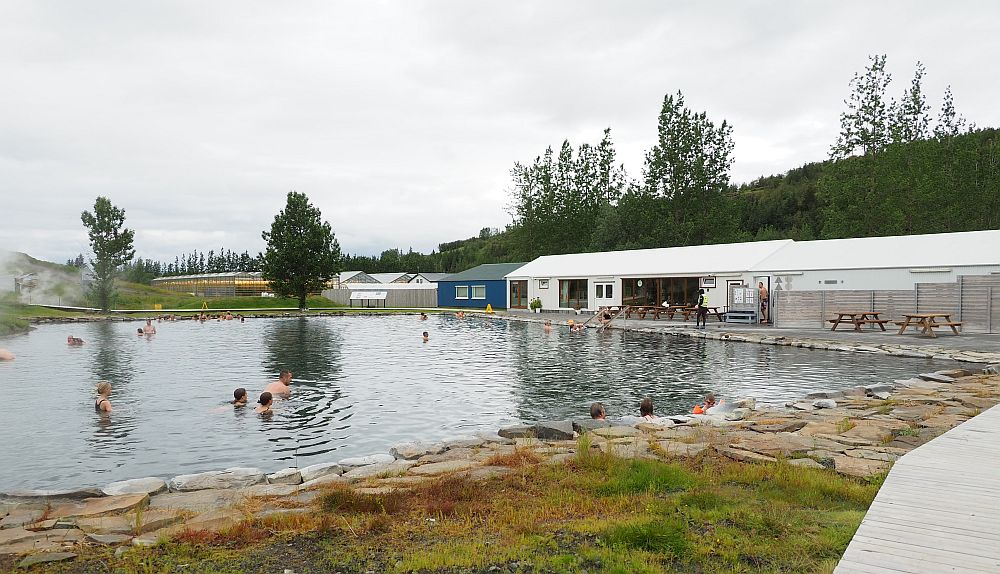 The pool is more or less square, edged with rocks. To the right is a long, low building with a white roof, a few picnic tables in front of it.