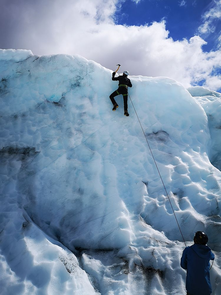 A wall of bluish-white ice. Near the top, a man (Albert), clings to the ice, his feet (crampons) in the ice, about to pound the ice above him with a small pickaxe. He is attached to a rope, which extends down to a person at the bottom of the picture.