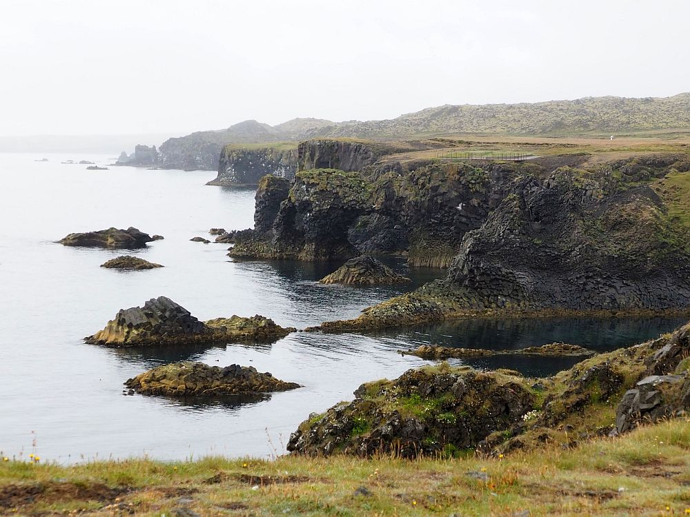 The coastline isn't straight but is lined with cliffs that extend in someplaces outwards, sometimes have little bays between them. Flat on top, steep cliffs down to the water. It's a gray day, so the coast in the background is misty.