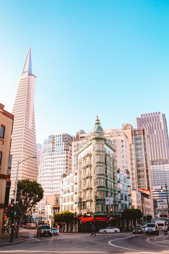 In the center, the Sentinal building is triangular, its sharpest point at the intersection of two streets. Traffic waits at its base while pedestrians cross. To the left of the picture is the Transamerica pyramid in the distance, along with a jumble of less distinctive tall buildings.