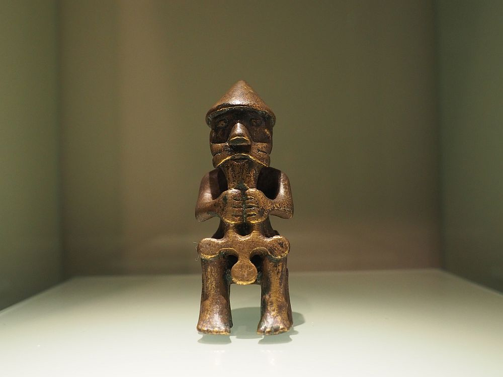 The figure is in a sitting position facing the camera. It wears a pointy hat, has a mustache, and holds the hammer or cross in both hands in front. It reaches from his chin to his knees.