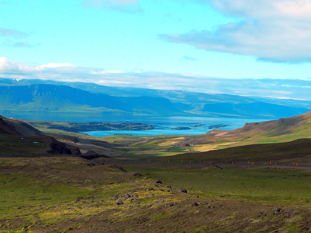 A valley down the center of the shot allows a view down to a fjord, hills on either side, blue water at the bottom.