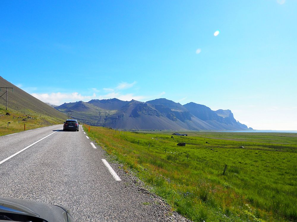 Ahead, a paved road with one other car. To the right, a green field. Beyond that, in the distance ahead, a clump of mountains.