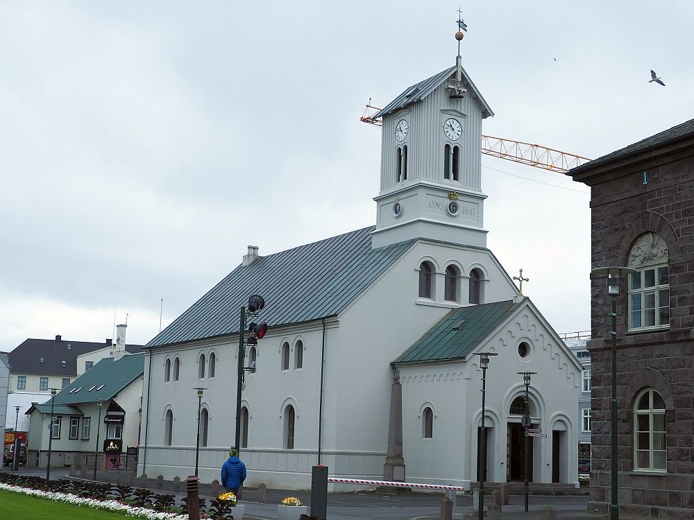 The church is white and a simple design: a peaked roof down the center and a square short tower at one end. The entrance extends outward and is smaller, so the peak of its roof is lower.