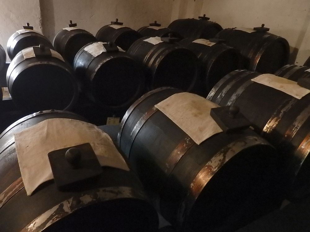 Barrels lie on their sides in rows. On top of each is a square white cloth.