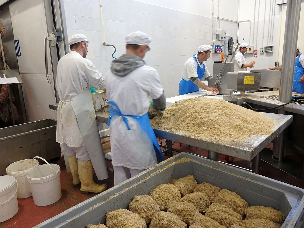 In the background, 2 men in white clothes, wearing aprons, work at a pile of brownish salt on a table. Beyond them are two more men at a conveyer belt, one of them feeding a chunk or leg of meat into a machine. In the foreground is a bin with a bunch of salt-covered round pieces or legs of meat packed in closely.