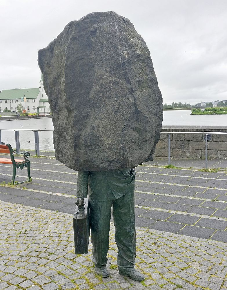 The bottom half of the statue is bronze and looks like the bottom half of a man wearing business clothes: neat trousers, work shoes, and in one hand, a briefcase. The top half is a huge stone: granite, I think, and just a rough, natural shape.