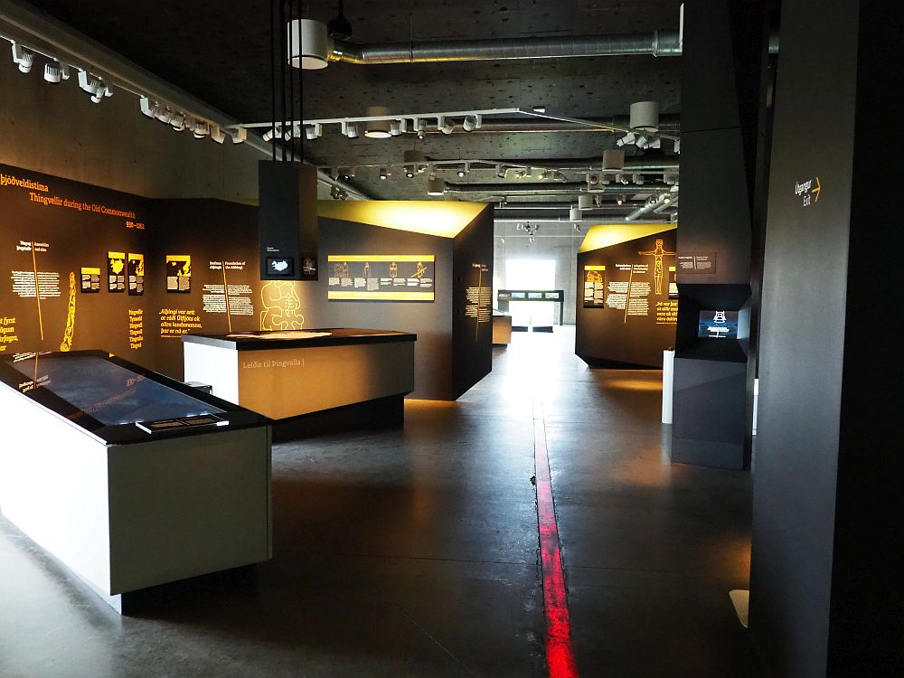 A long dark room with a black ceiling and floor, and a red lit-up line extending from the bottom of the photo to the end of the room. Lights expose various signs along the walls. Big blockish scrreen tables here and there, each with a slightly slanted top.